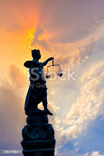 silhouette of Lady Justice at the fountain at Romerberg in Frankfurt, Germany
