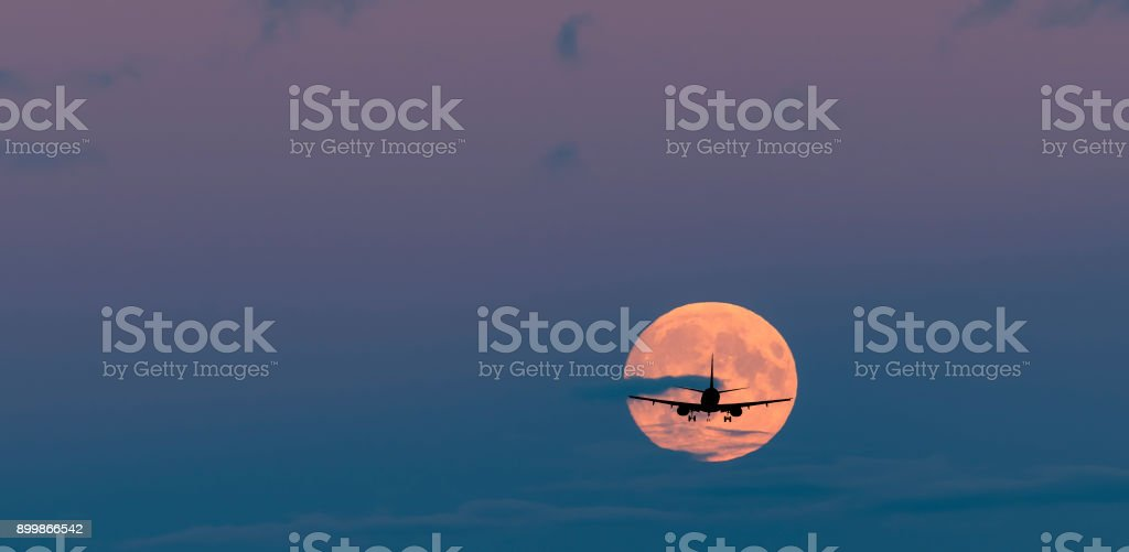 Silhouette of landing airplane at dawn stock photo