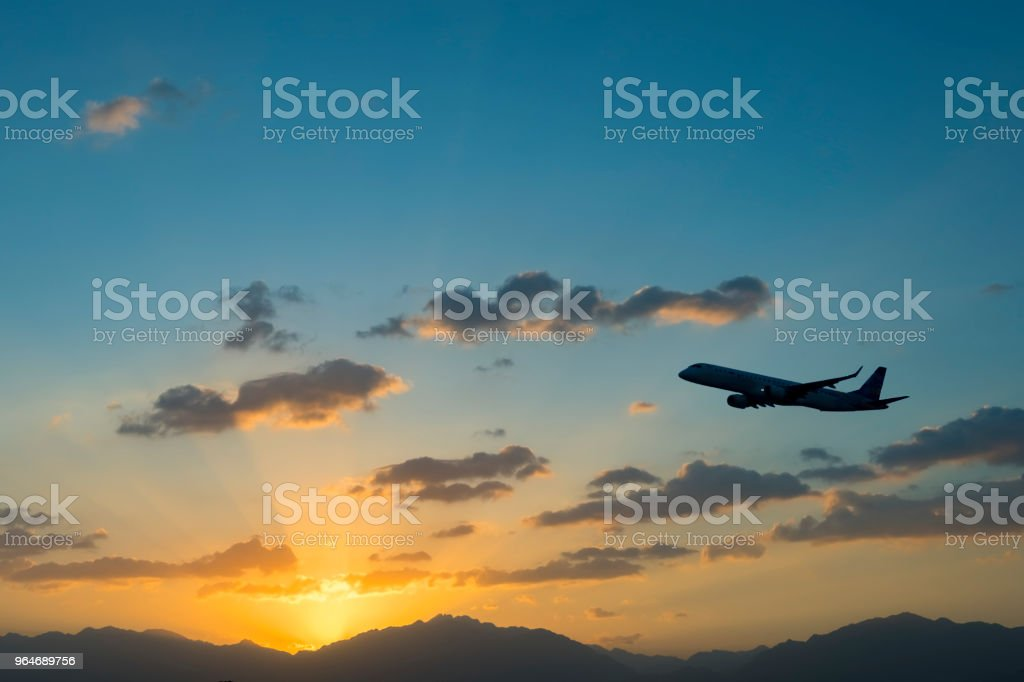 Silhouette of landing airplane at dawn royalty-free stock photo
