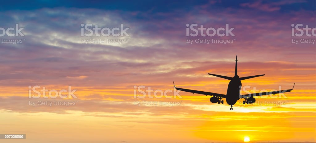 Silhouette of landing airplane stock photo