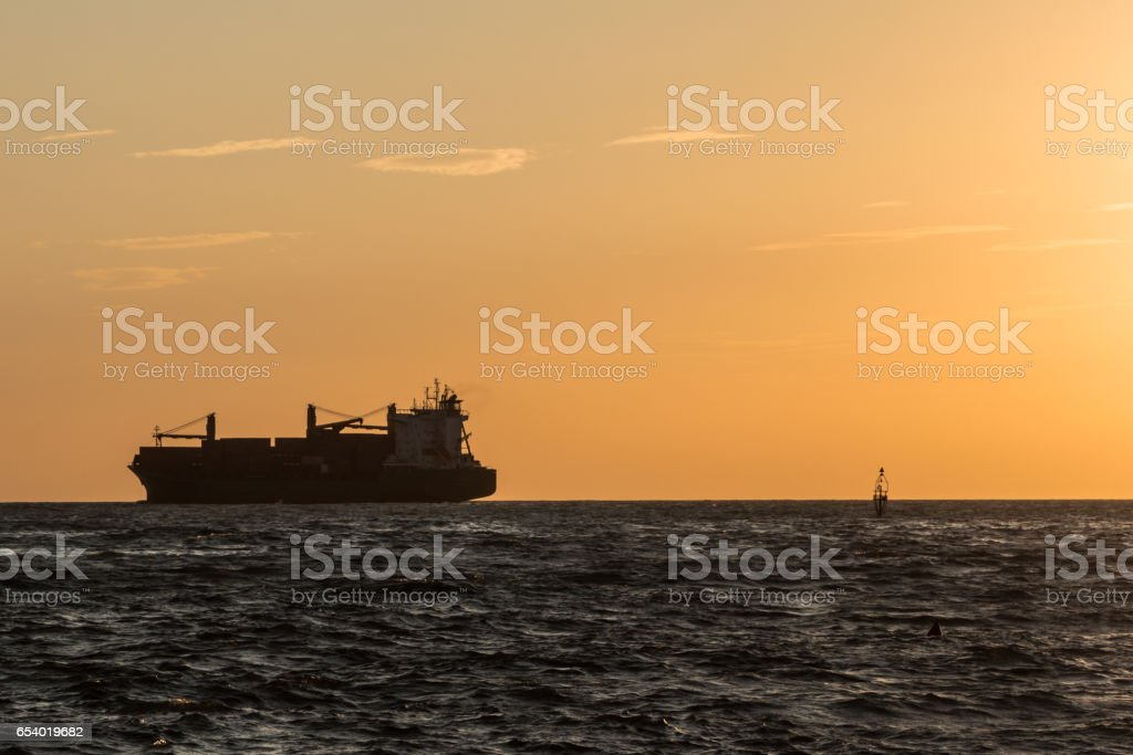 Silhouette of Large Red Container Ship Near Coastline at Sunset stock photo