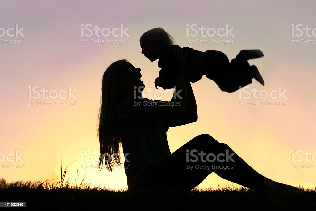 Silhouette of Laughing Mother and Baby Playing Outside stock photo
