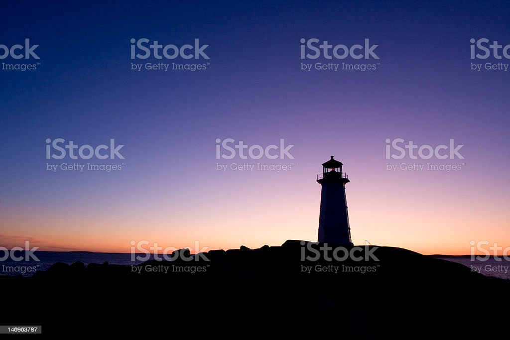 Silhouette of lighthouse against backdrop of rich sunset royalty-free stock photo