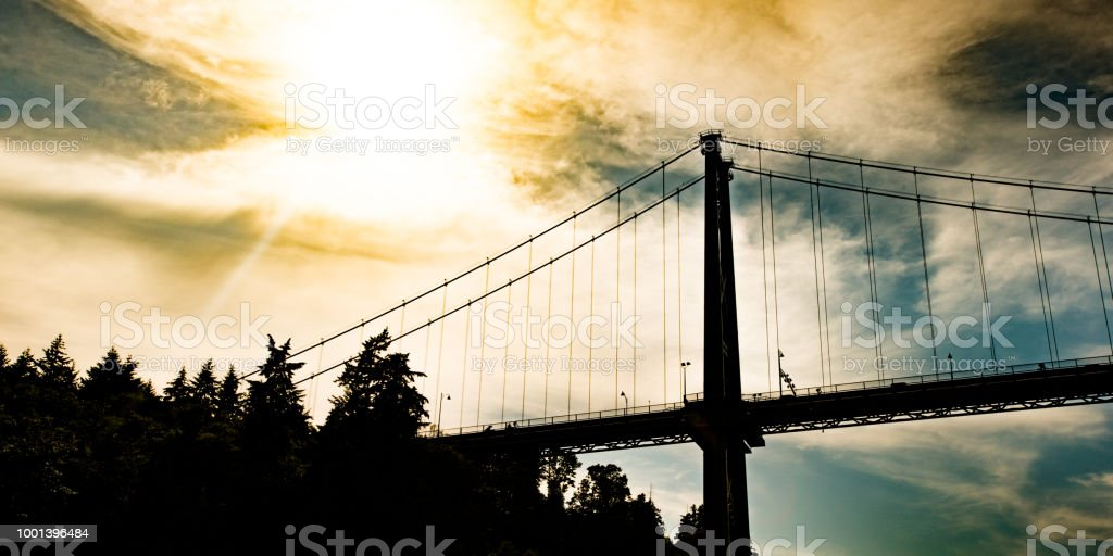 Silhouette of Lions Gate suspension bridge in West Vancouver. stock photo