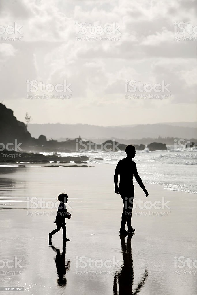 Silhouette of Little Boy Following His Father on Beach royalty-free stock photo