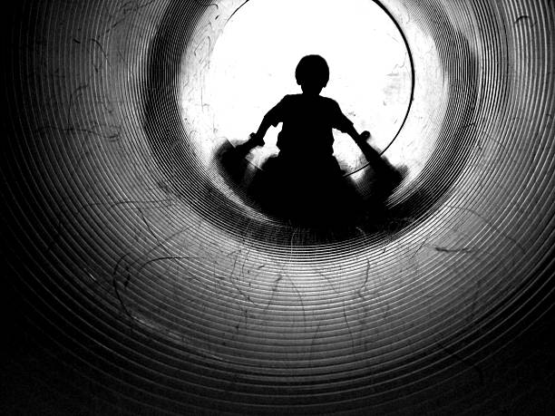 Silhouette of Little Boy Going Down Tunnel, Black and White stock photo