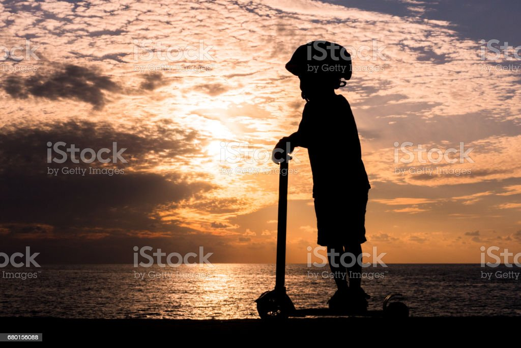 Silhouette of little boy on scooter against background of sea sunset stock photo