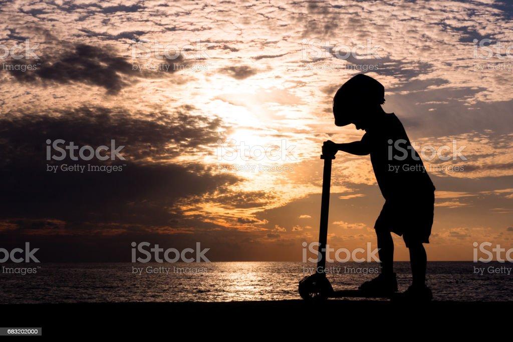 바다 일몰의 배경 스쿠터에 서 있는 어린 소년의 실루엣 royalty-free 스톡 사진