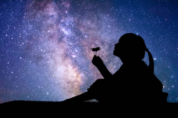 silhouette of little girl holding a flower - shooting stars stock photos and pictures
