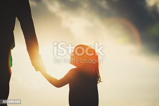 istock silhouette of little girl holding parent hand at sunset 831688498