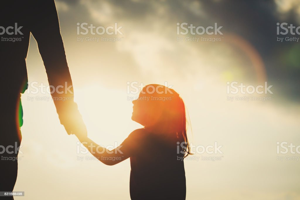 silhouette of little girl holding parent hand at sunset stock photo