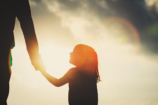 Silhouette Of Little Girl Holding Parent Hand At Sunset - Fotografie stock e altre immagini di Accudire