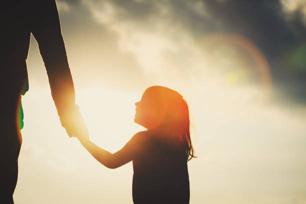 silhouette of little girl holding parent hand at sunset - father and daughter stock photos and pictures