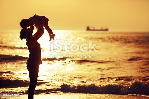 istock Silhouette of little girl playing near the sea on sunset 490475752