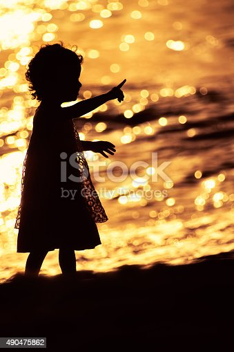 istock Silhouette of little girl playing near the sea on sunset 490475862