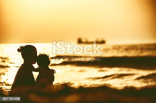 istock Silhouette of little girl playing near the sea on sunset 537161438