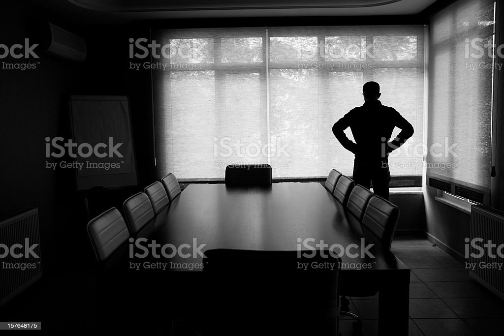 Silhouette Of Lonely Businessman Standing By Boardroom Table In Office stock photo