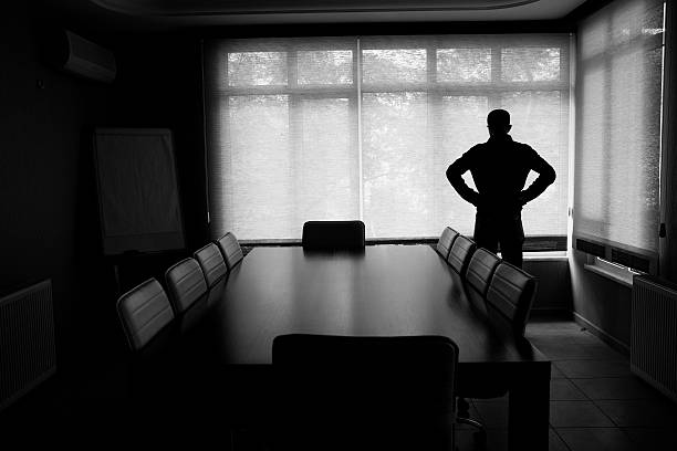 silhouette of lonely businessman standing by boardroom table in office - bankruptcy stock pictures, royalty-free photos & images