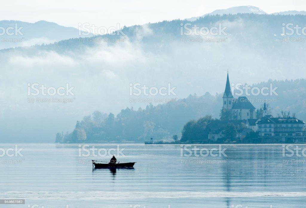 Silhouette der einsamer Fischer sitzen im Ruderboot mit Reflektion auf See im Sonnenlicht des nebligen Morgen – Foto