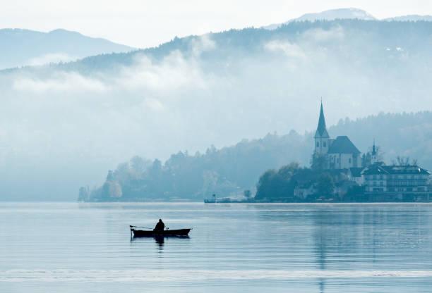 silhouette der einsamer fischer sitzen im ruderboot mit reflektion auf see im sonnenlicht des nebligen morgen - wörthersee stock-fotos und bilder