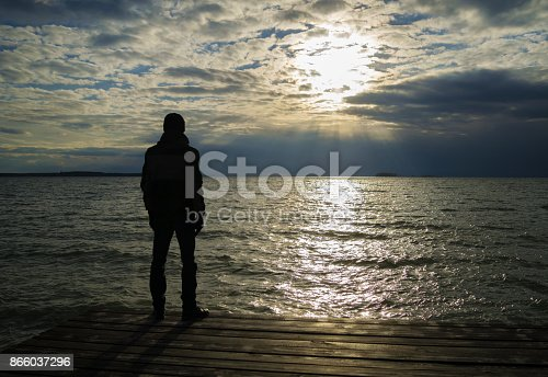 Silhouette of lonely man in jacket and cap who standing on wooden dock and looking on sunset over ocean. Cloudy weather.