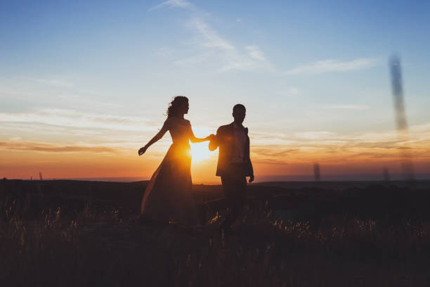 Silhouette of loving couple in rays of sun. Newlyweds walking outside Silhouette of loving couple in rays of sun. Newlyweds walking outside sun shining through dresses stock pictures, royalty-free photos & images