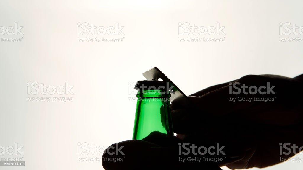 Erkek silüeti açılış kahverengi bira şişe açacağı ile eller royalty-free stock photo
