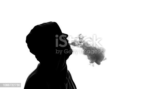 istock Silhouette of male in hood exhaling electronic cigarette smoke, modern devices 1066732730
