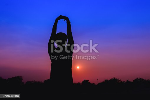 873786782istockphoto Silhouette of male meditating and yoga practicing with exercise at sunrise in public park morning 973637650