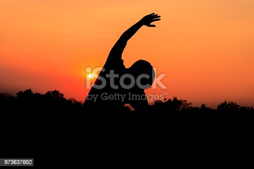873786782istockphoto Silhouette of male meditating and yoga practicing with exercise at sunrise in public park morning 973637652