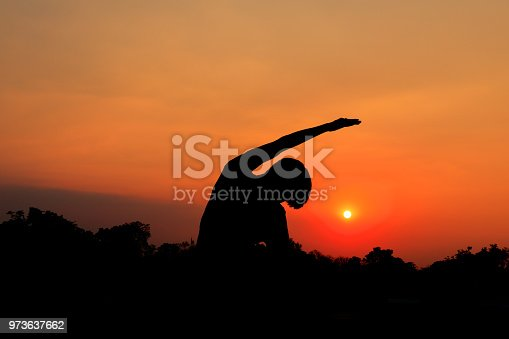873786782istockphoto Silhouette of male meditating and yoga practicing with exercise at sunrise in public park morning 973637662