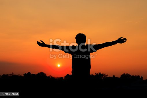 873786782istockphoto Silhouette of male meditating and yoga practicing with exercise at sunrise in public park morning 973637664