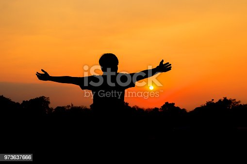 873786782istockphoto Silhouette of male meditating and yoga practicing with exercise at sunrise in public park morning 973637666