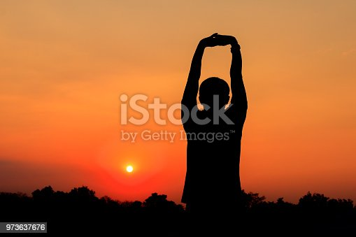 873786782istockphoto Silhouette of male meditating and yoga practicing with exercise at sunrise in public park morning 973637676