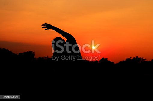 873786782istockphoto Silhouette of male meditating and yoga practicing with exercise at sunrise in public park morning 973640332