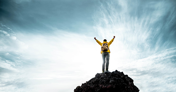 Silhouette of male on the mountain with open arms - Successful hiker exult on the top of the rock - Leadership concept