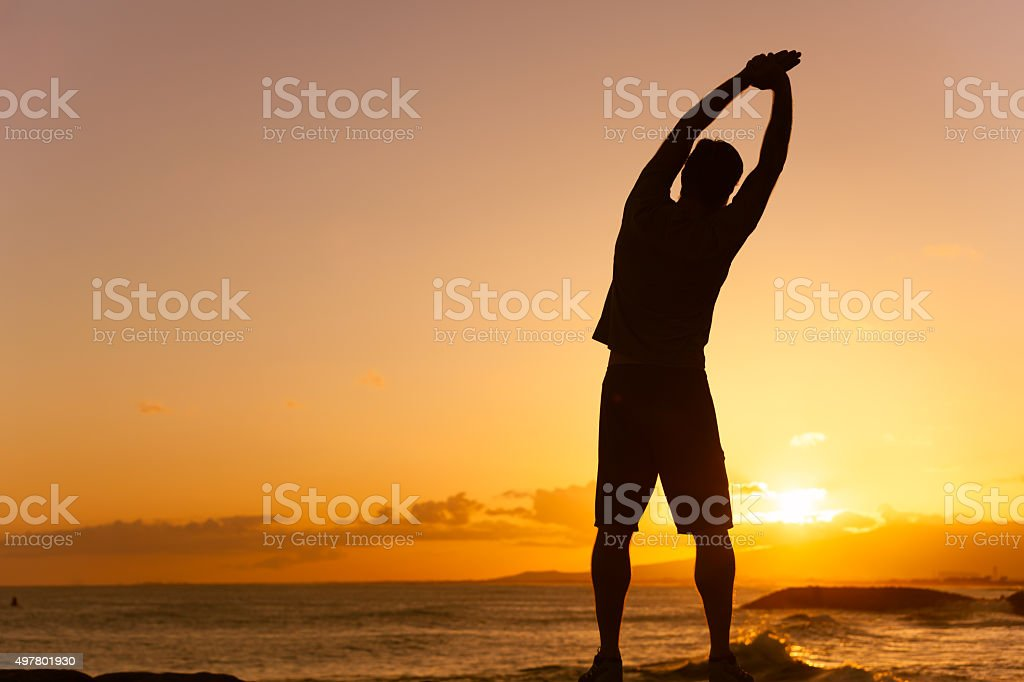 Silhouette of male stretching outdoors stock photo