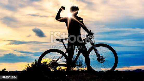 istock silhouette of man and bicycle on sunset sky 992551634