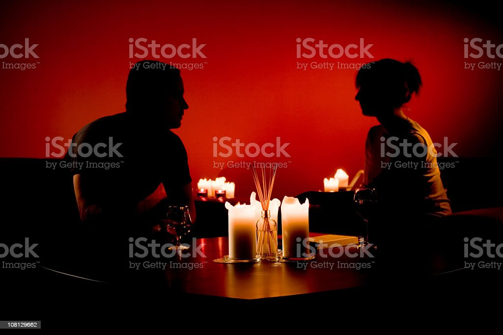 Silhouette of Man and Woman Sitting by Various Candles stock photo