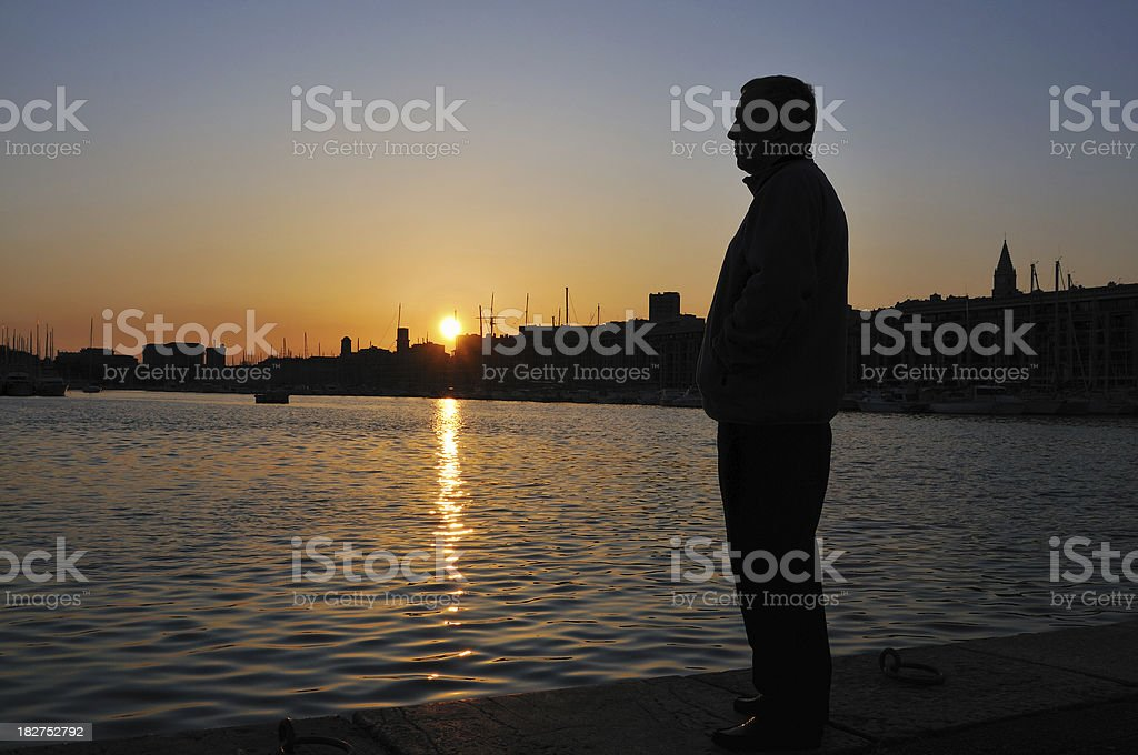 Silhouette of man at sunset in old port stock photo