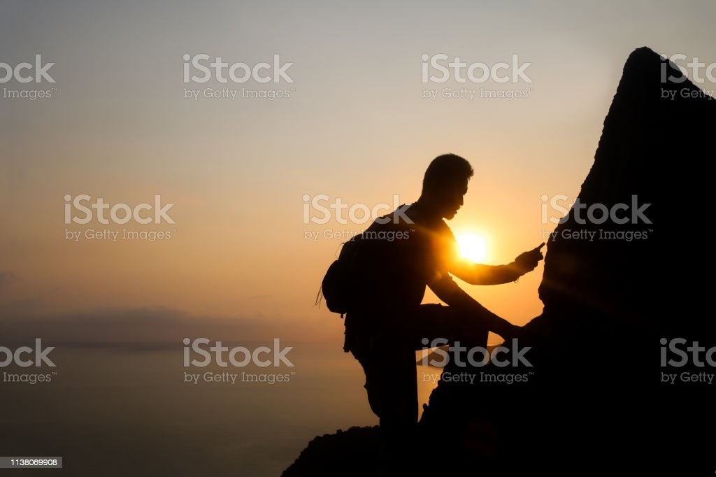 Silhouette of man climbing rock, Photographer on the mountain at...