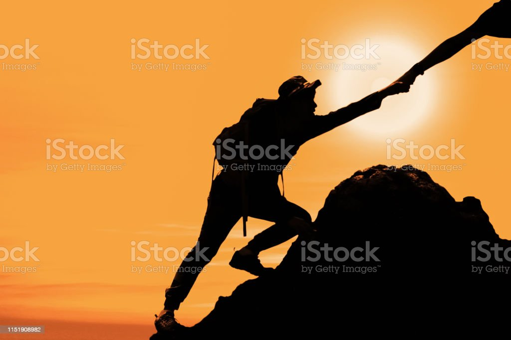 silhouette of man climbing up mountain with hand giving help in warm...
