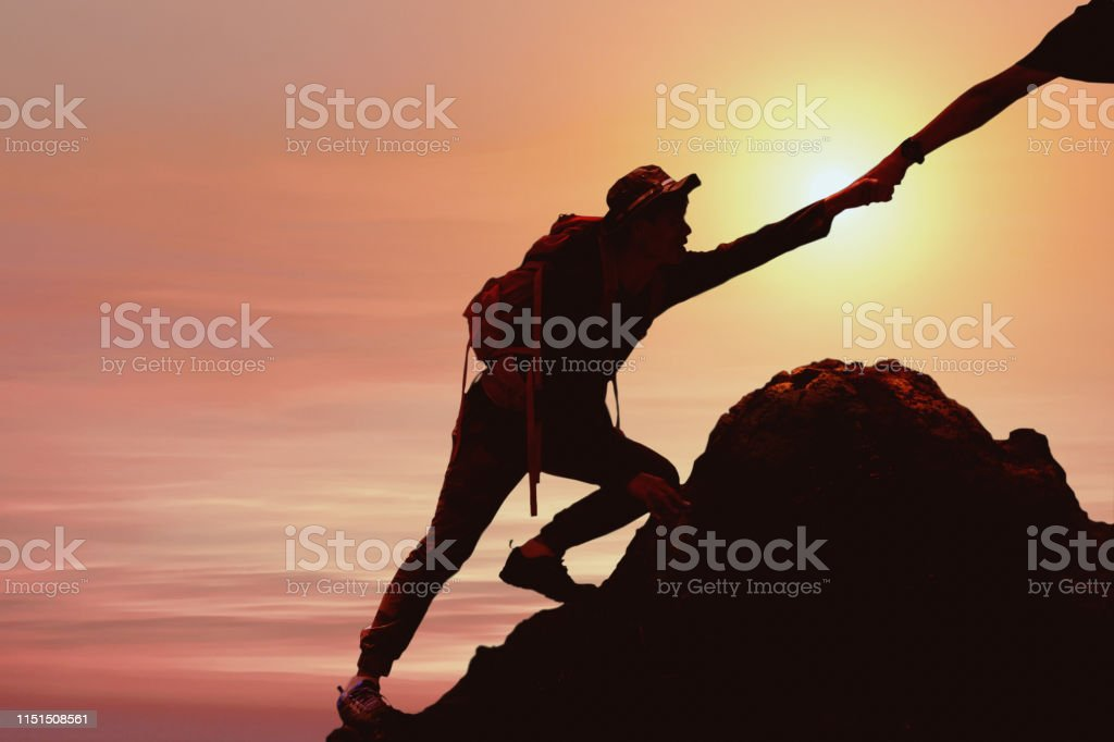 silhouette of man climbing up mountain with hand giving help