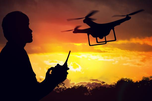 Silhouette of man controlling a drone at sunset. stock photo