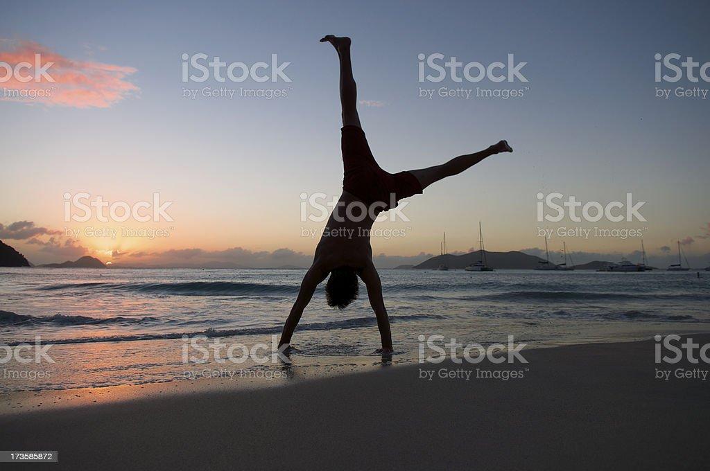 Silhouette of Man Doing Cartwheel on Sunset Beach royalty-free stock photo