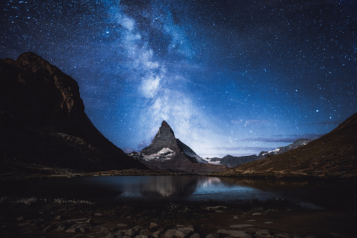 Man exploring the Zermatt area in Switzerland at night - looking at starry sky and Milky Way near the Matterhorn and Riffelsee lake in Gornergrat area - summertime