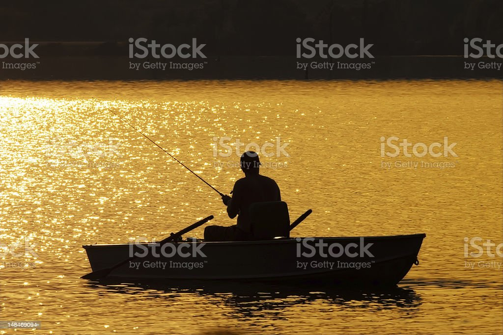 Silhouette of man fishing in boat at sunset royalty-free stock photo