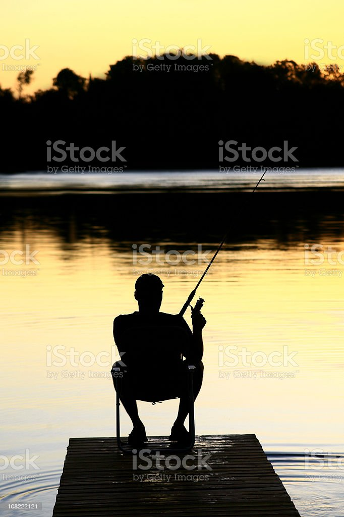 Silhouette of man fishing off the dock at sunset royalty-free stock photo