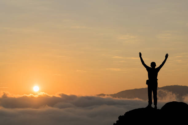 silhouette of man hold up hands on the peak of mountain,success concept - conquering adversity stock photos and pictures