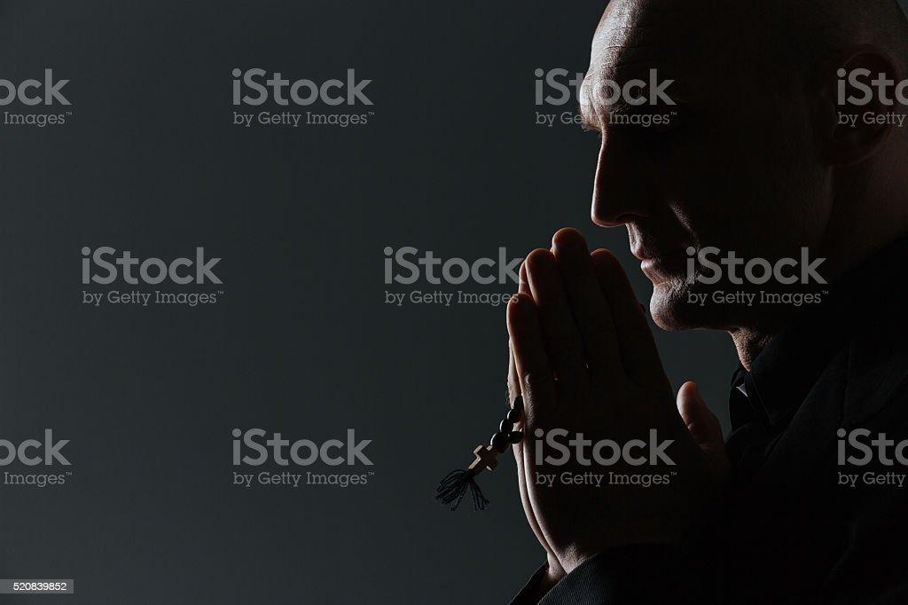Silhueta de homem segurando de terço e orar - foto de acervo